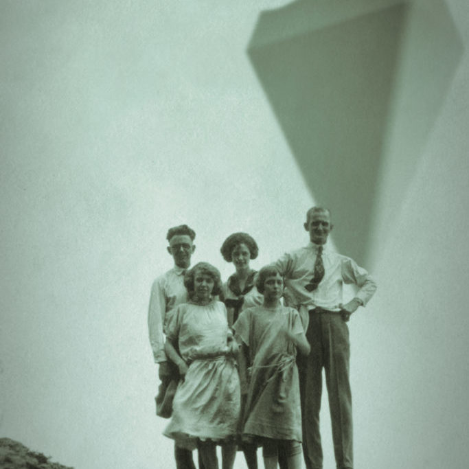 A family poses with the anomaly in view on a beachside rock.