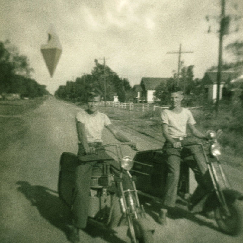 Two young men on Cushman motorcycles pose in the street, the anomaly watches over them in the distance.