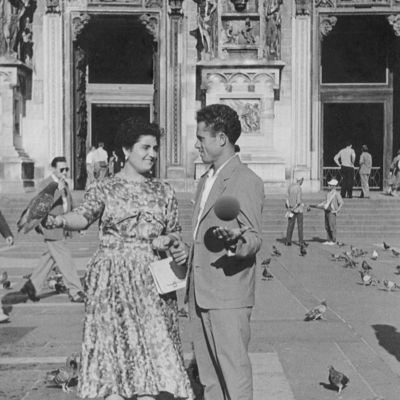A couple stands in front of italian architecture, a pigeon in the womans hand, a levitating orb in the mans.