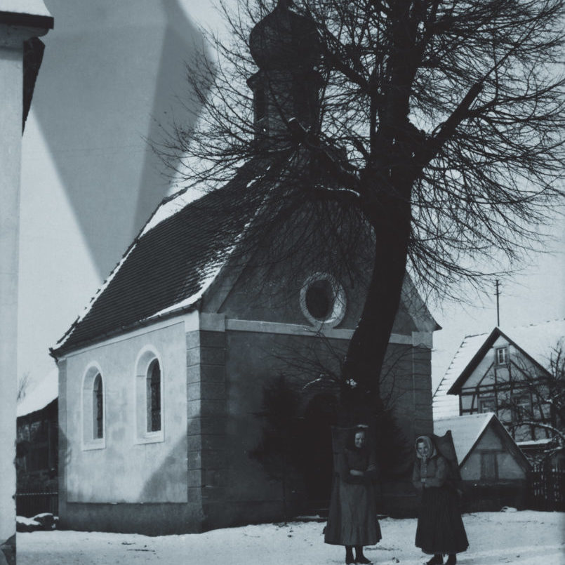 Two german women stand in front a church, with the anomaly looming overhead.